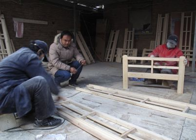 Wang Le (C), who sells his furniture products through China's largest consumer-to-consumer e-commerce platform Taobao, makes beds alongside other workers in a workshop in Dongfeng Village, Jiangsu province December 19, 2011. Intense competition has fuelled price wars among furniture vendors. That, combined with fee hikes from China's leading online e-commerce platform, Taobao Mall, this year forced the closure of some of fledgling businesses in this dusty village that is home to more than 1,000 Taobao furniture sellers. Picture taken December 19, 2011.